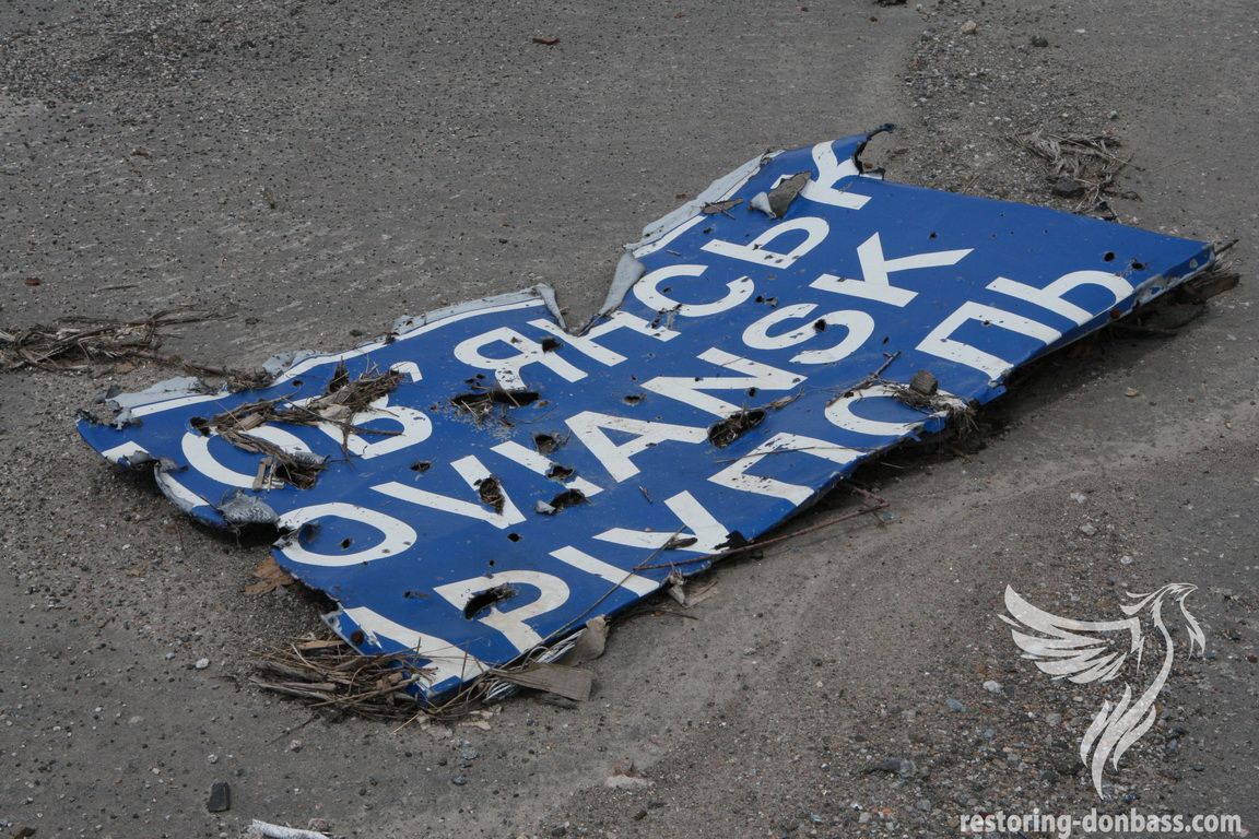 Road sign, damaged by shells, area of the Donetsk airport